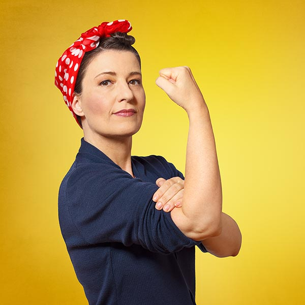 A woman with a bended right hand showing her muscle strength