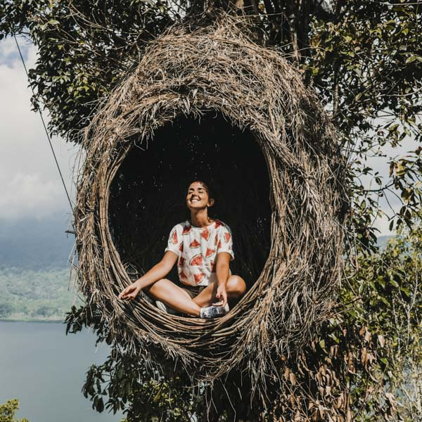 Woman sat inside a tree meditating