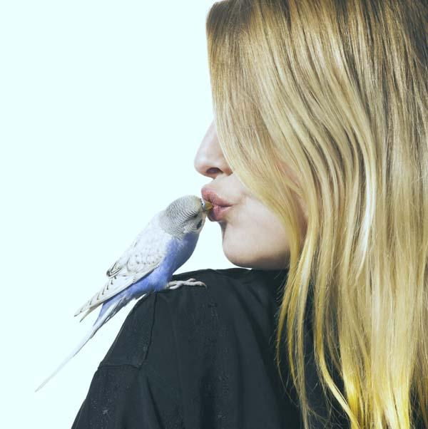 Woman kissing a bird