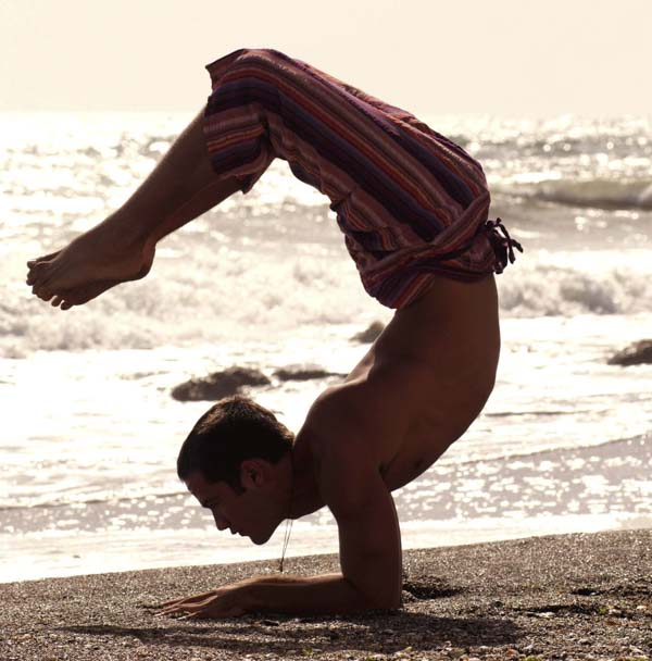 Men doing yoga at the beach
