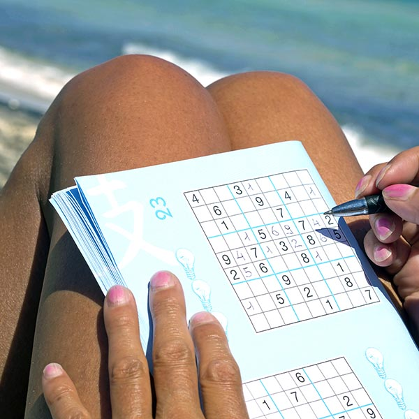 woman on the beach doing crosswords