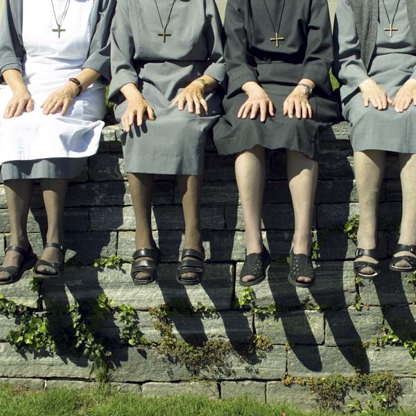 A group of nuns sitting on a wall