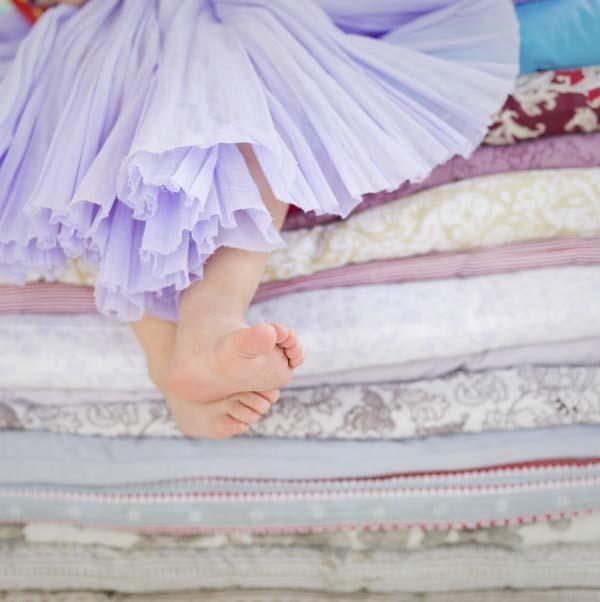 Princess sitting on dozens of mattresses