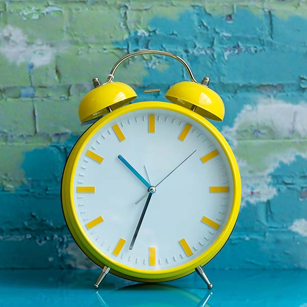 Big yellow alarm clock on blue background