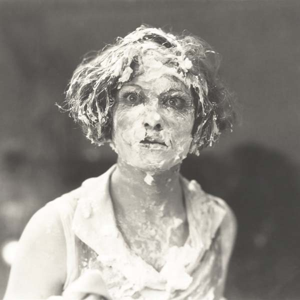 Woman's face covered in whipped cream