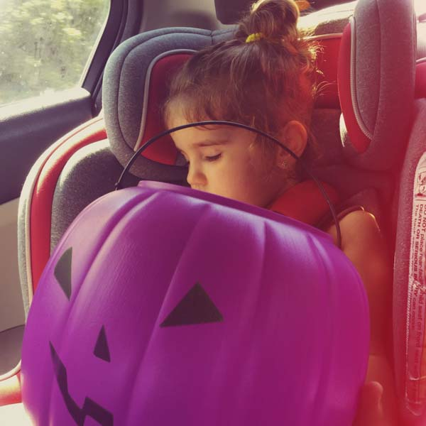 Little girl in car seat sleeping after Halloween party