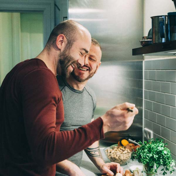 Gay couple in kitchen cooking together