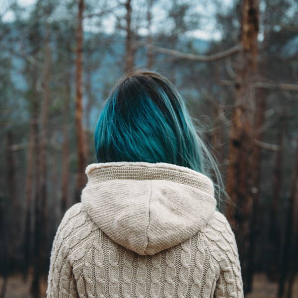 Woman with blue hair looking out at forest