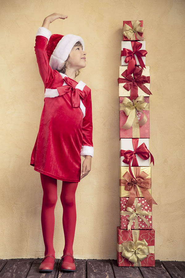 Girl measuring her growth by Christmas packages