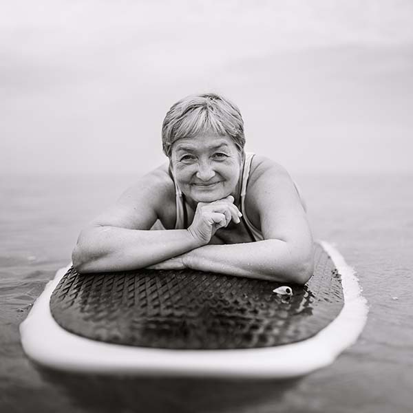 Black and white image of happy senior woman relaxing on paddleboard