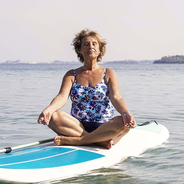 Senior woman meditating on stand up paddleboard
