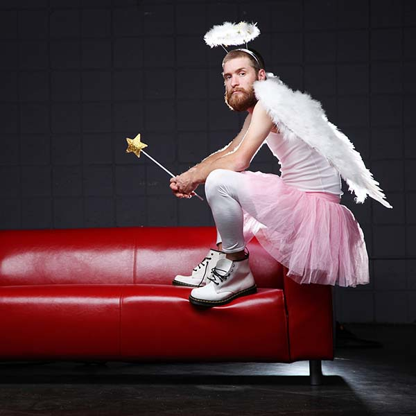 Man dressed as angel sitting on couch