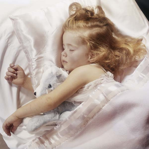 Little girl dreaming on satin pillow