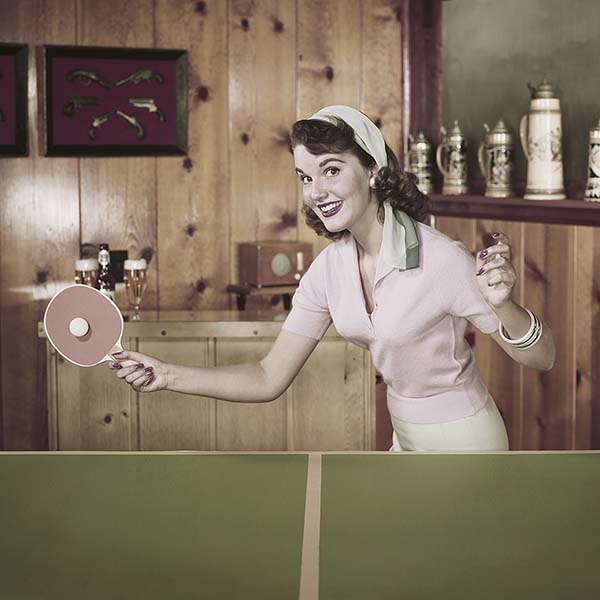 Retro woman smiling and playing ping pong