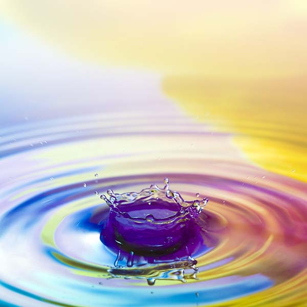 Water drop with rainbow ripples