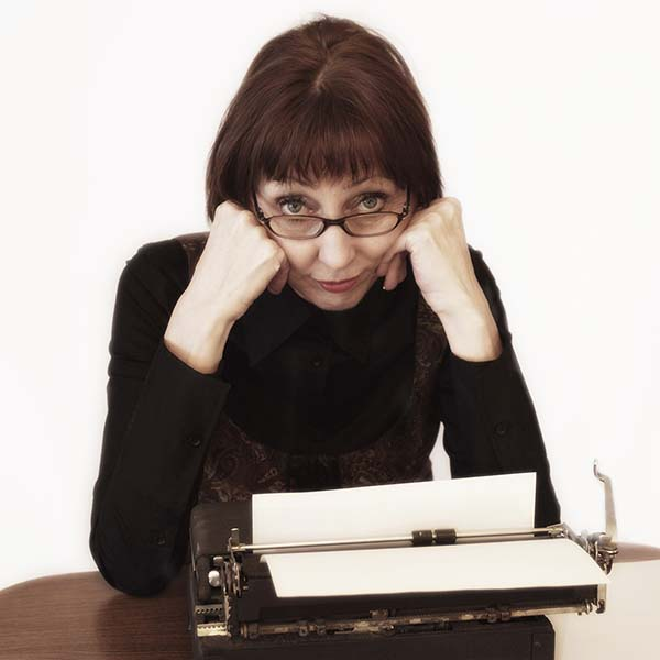 Middle aged woman using antique typewriter