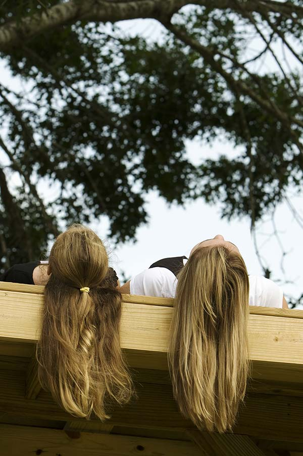 Two friends looking up at clouds, hair hanging off pier