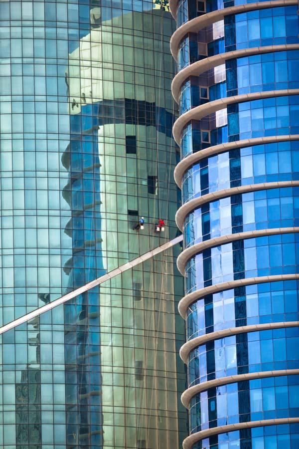 Window washers washing rounded windows on high rise