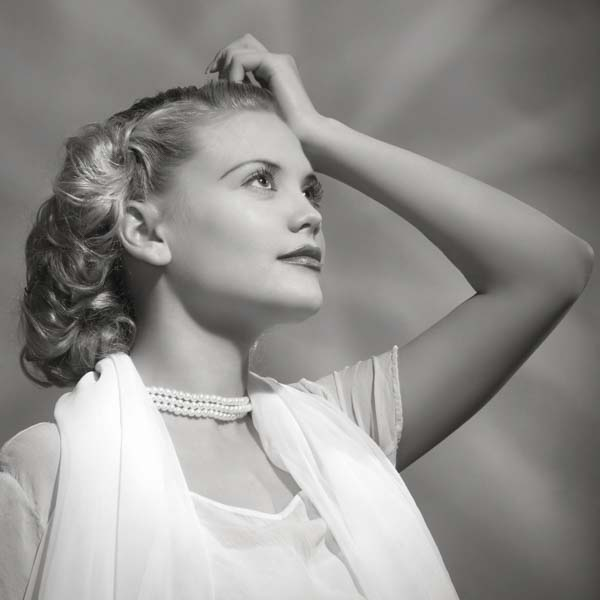Vintage woman looking up at rays of light