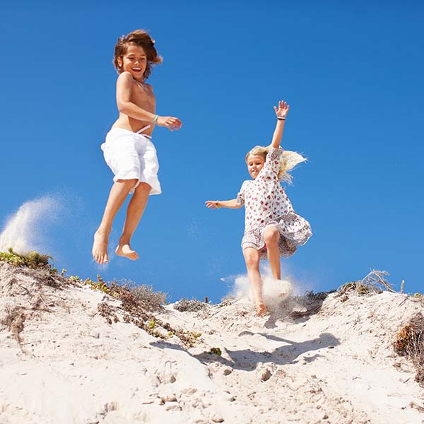 Boy and girl jumping down sand dune