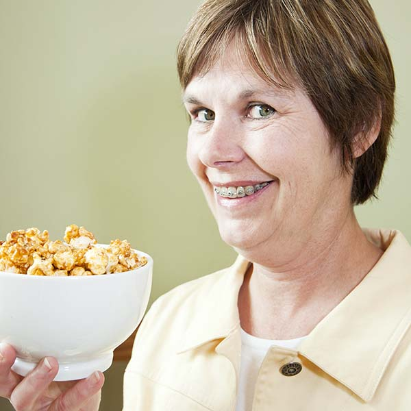 Woman with braces holding caramel corn
