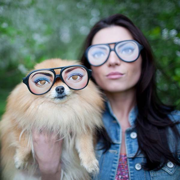 Woman and dog wearing funny glasses