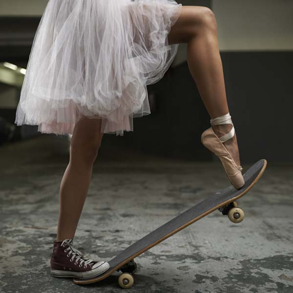 Ballerina wearing tennis shoe and ballet slipper on skateboard