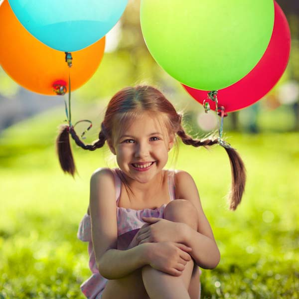 Little girl with balloons lifting her pigtails