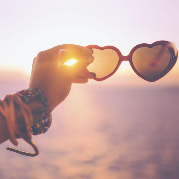Heart-shaped sunglasses at sunrise