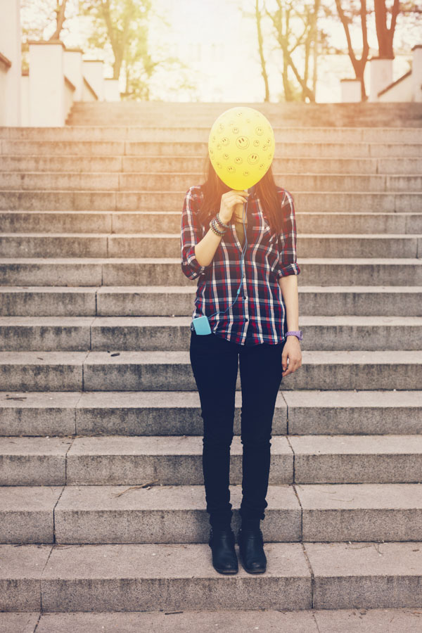 Woman holding happy face balloon in front of her face