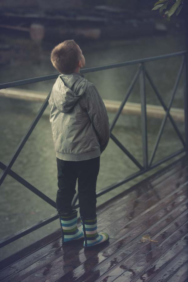 Little boy in rubber rain boots looking up at sky