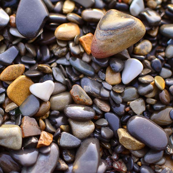 A natural heart-shaped pebble on beach