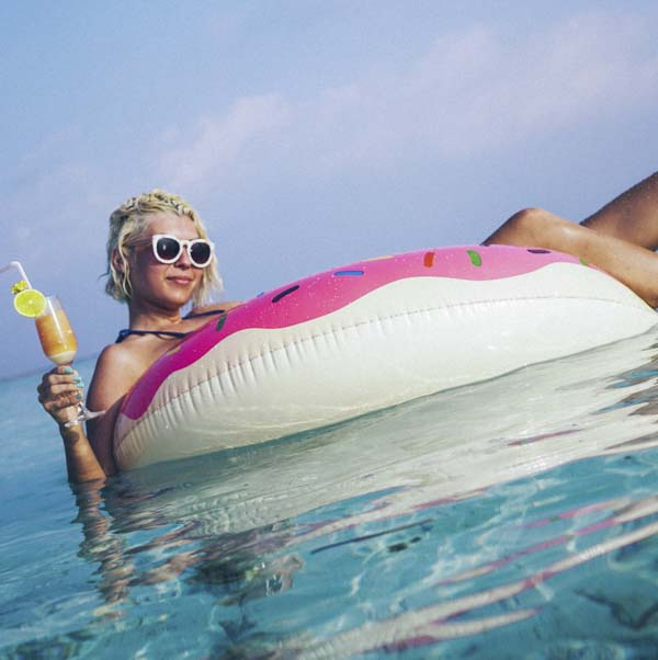Woman floating on donut inflatable in ocean