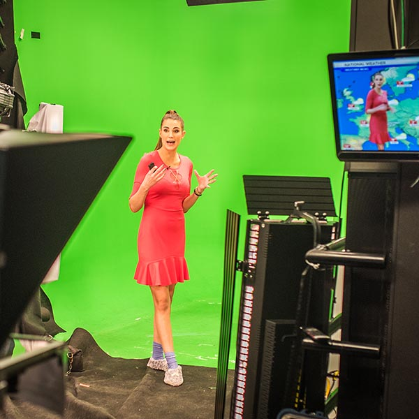 Weather woman in front of green screen