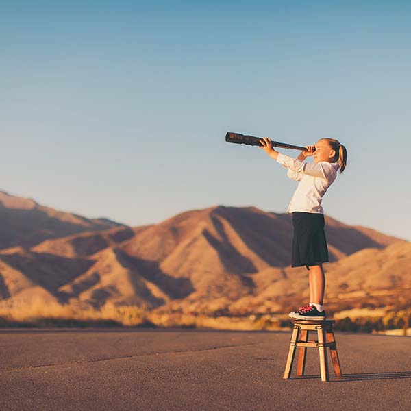 Confident young girl standing on stool looking through telescope