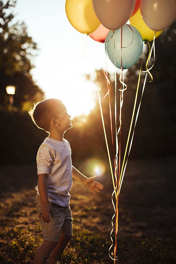 Happy child receiving balloons