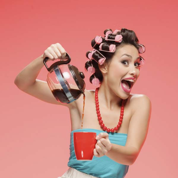 Happy woman in curlers pouring coffee