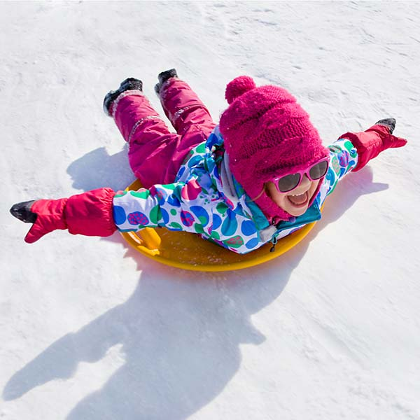 Girl on disc riding down snowy slope