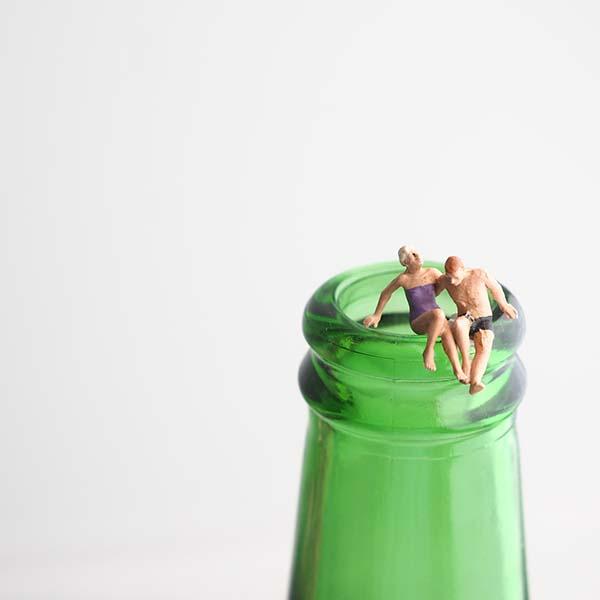 Miniature swimmers on rim of bottle