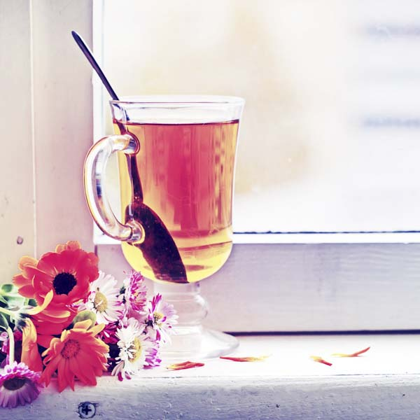 Tea and flowers in windowsill