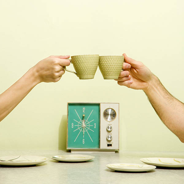 Vintage couple drinking coffee with transistor radio on table