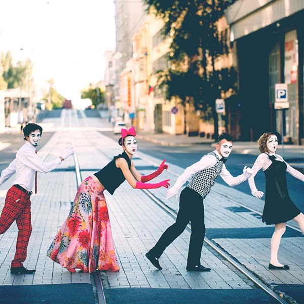 Four street mimes walking