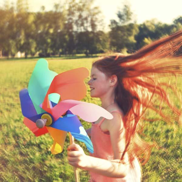 Girl running fast with pinwheel