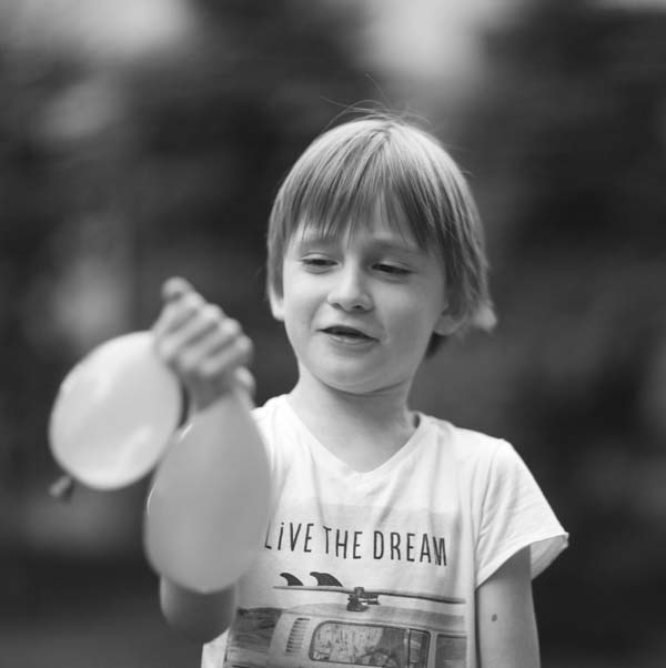 Kid squeezing water balloon
