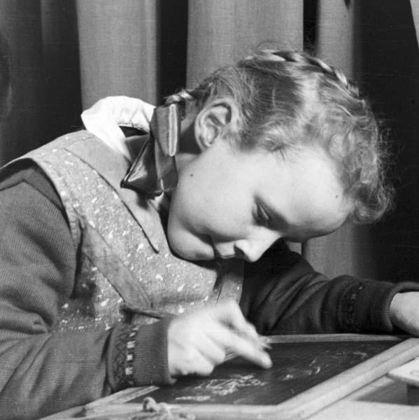 Vintage girl in school drawing on slates