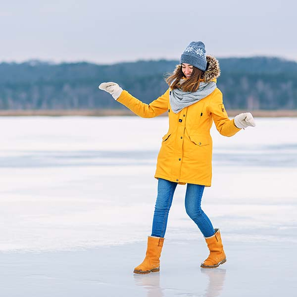 Woman laughing and trying to walk on ice