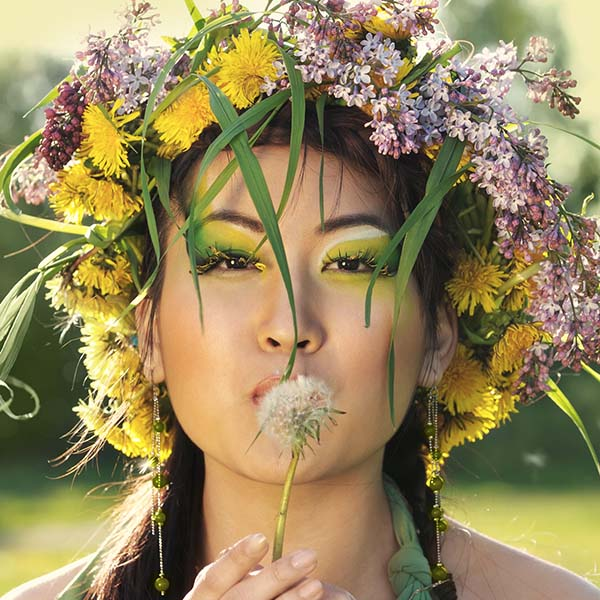 Woman with wreath of flowers on head blowing on a dandelion