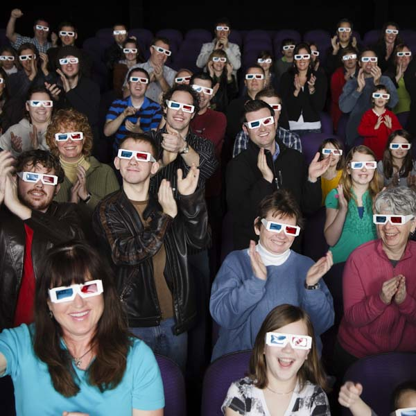 Audience in theater wearing 3D glasses and clapping