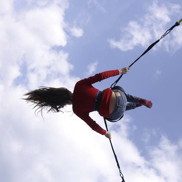 Woman acrobat in the air with ropes