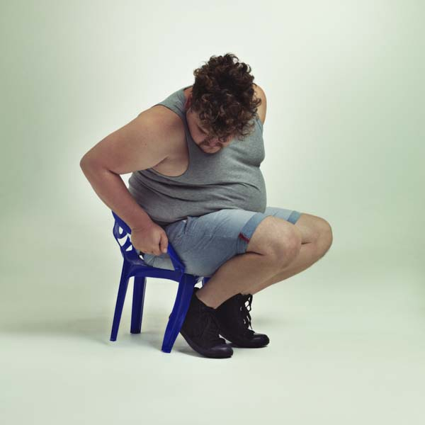 Man trying to fit in chair too small